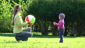 The young woman plays a ball with the little girl stock video footage