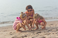 Young woman plays on the beach with two little girls Stock Photos