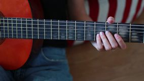 Young woman plays guitar and touches strings. Young woman with bracelet on her hand plays guitar and touches strings stock video