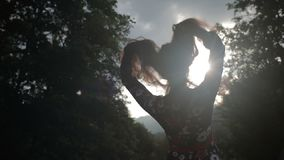 Young woman plays with her hair in sunbeams. Silhouette