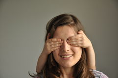 A young woman plays hide and seek with her son Stock Photo