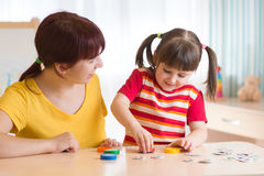 Young woman plays with kid educational game. Young women plays with kid educational game in nursery stock image
