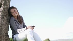 A young woman plays on a mobile phone. She sits under a tree in a field by the sea and smiles. The girl writes a message on the phone in nature stock footage