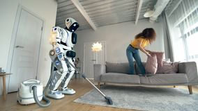 Young woman plays with pillows while white robot does vaccum cleaning. stock video footage