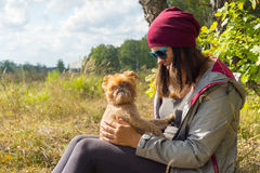 Young woman plays with small dog Royalty Free Stock Image