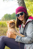 Young woman plays with small dog Stock Images