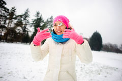 Young woman plays with someone in snowballs. The first snow and winter entertainments very much please. The woman likes to play snowballs. She happily smiles Stock Images