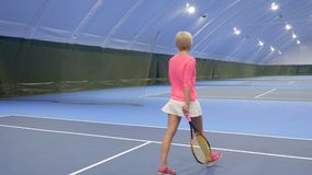 Young woman plays tennis at the indoors court. Young woman wearing sportswear plays tennis at tennis court. Woman is a trainer at the courts and professionally stock footage