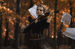 Young woman plays violin over the music flying notes Royalty Free Stock Images