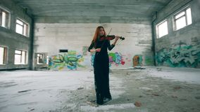 Young woman plays wooden violin in a dark room, standing alone. stock video