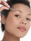 Young Woman plucking Eyebrow Royalty Free Stock Photography
