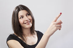 Young woman pointing. Against a plain background Stock Photography