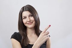 Young woman pointing. Against a plain background Stock Image