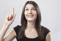 Young woman pointing. Against a plain background Royalty Free Stock Images