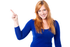 Young woman pointing away over white Royalty Free Stock Images