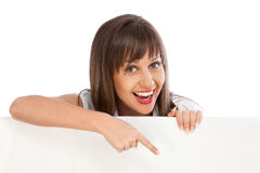 Young woman pointing behind billboard Stock Image