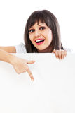 Young woman pointing behind billboard. Young woman pointing behind white billboard isolated on white background Stock Images
