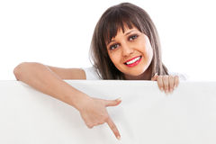 Young woman pointing behind billboard Royalty Free Stock Photos