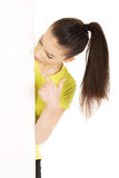 Young woman pointing on blank board. Royalty Free Stock Photo
