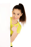 Young woman pointing on blank board. Stock Photo