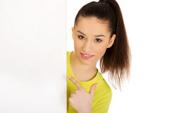 Young woman pointing on blank board. Stock Image