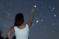 Young woman pointing on defocused Star. Woman under starry night, Woman pointing to Defocused  Scorpius Constellation Stock Image