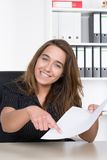 Young woman is pointing at a document with her finger Royalty Free Stock Image