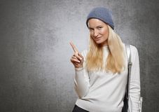 Young woman pointing finger at copy space. On a concrete gray background Royalty Free Stock Photography