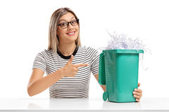 Young woman pointing at garbage bin full of shredded paper Royalty Free Stock Image