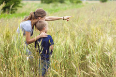 Young woman pointing hand and little boy her son standing in whe Stock Image