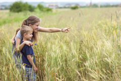 Young woman pointing hand and little boy her son standing in whe Stock Photos