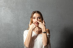 Young woman pointing at her nose with fingers Royalty Free Stock Photos