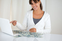 Young woman pointing laptop screen with cash money. Portrait of a young woman pointing laptop screen with cash money while is smiling and looking at you Stock Image
