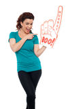 Young woman pointing at large foam hand Royalty Free Stock Photos