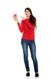 Young woman pointing on piggybank. Stock Photos