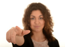 Young woman pointing. Portrait of a young woman pointing with her finger on a white studio background Stock Image