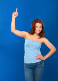 A young woman pointing at something, isolated on blue background Stock Photography