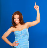 A young woman pointing at something, isolated on blue background Royalty Free Stock Photography