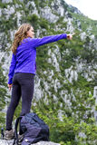 Young woman  pointing  while standing on a rock against amazing Royalty Free Stock Photo