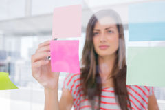 Young woman pointing sticky note with her pen Stock Photos