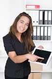 Young woman is pointing at a tablet with her finger Stock Image