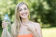 Young woman pointing to a bottle of water Royalty Free Stock Photo