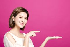 Woman pointing to somewhere, isolated on pink background Royalty Free Stock Images