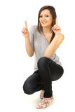 Young woman pointing up and looking at camera Stock Photo