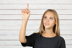 Young woman pointing up stock images
