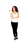 Young woman pointing up. Royalty Free Stock Image