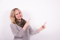 Young woman pointing on white background. Young happy woman pointing on white background and facing the camera Royalty Free Stock Photo