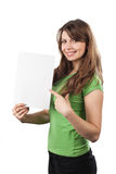 Young woman pointing at a white sign. Young smiling woman showing a white sign, isolated on white Royalty Free Stock Images