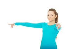 Young woman pointing on you and aside. Royalty Free Stock Photo
