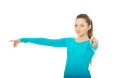 Young woman pointing on you and aside. Royalty Free Stock Photos